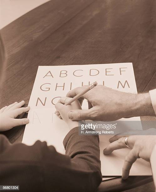 Child being helped man to print write the alphabet
