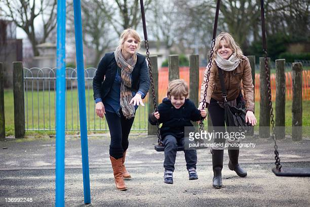 child being pushed on swing by two ladies - aunt fotografías e imágenes de stock