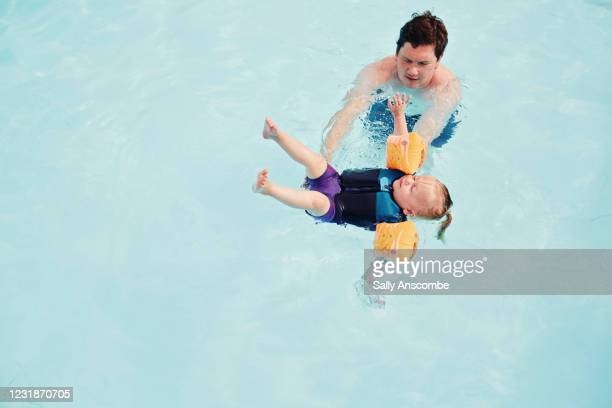 child being taught how to swim - girls stock pictures, royalty-free photos & images