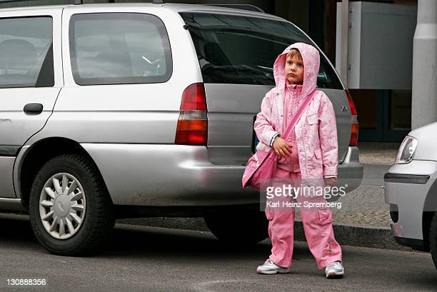 child between parking cars crossing the street, berlin, germany - avenida fotografías e imágenes de stock