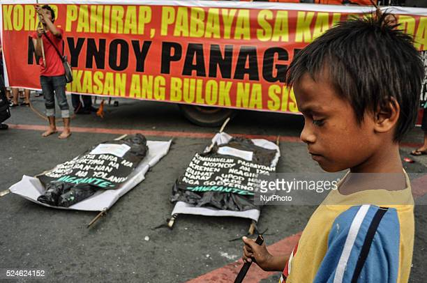 A child blinks as two mockup body bags are laid down in front of the stage depicting the body bags scattered at the typhoon devastated areas Militant...