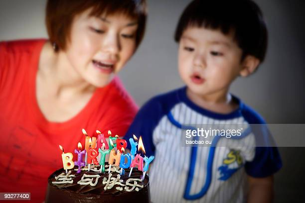 Child blowing birthday candles on the cake with hi