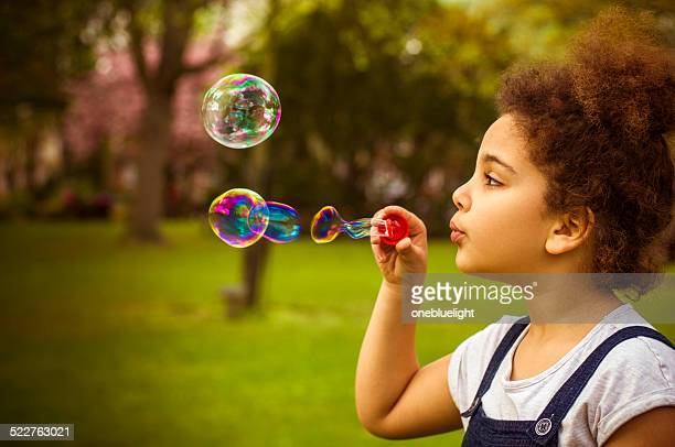 Child (7-8) Blowing Bubbles in Playground.