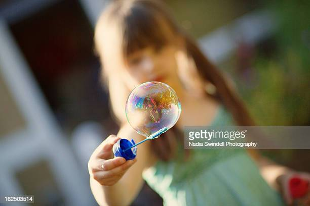 child blowing bubbles - weybridge stock photos and pictures