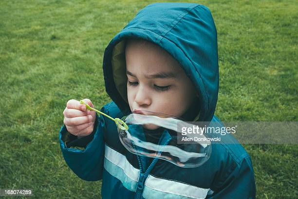 child blowing large bubble outside in rain