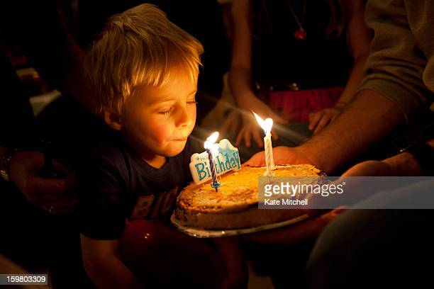 child blowing out candles on cake - birthday candles stock photos and pictures