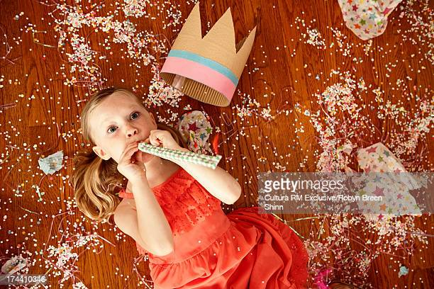 Child blowing party blower on wooden floor