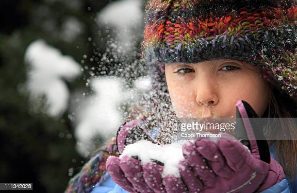 child blowing snow - cappi thompson stock pictures, royalty-free photos & images