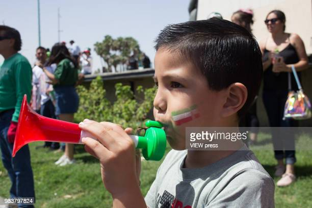 A child blows a bugle and People celebrate after winning their FIFA World Cup Group F South Korea vs Mexico match on June 23 2018 in Mexicali Mexico
