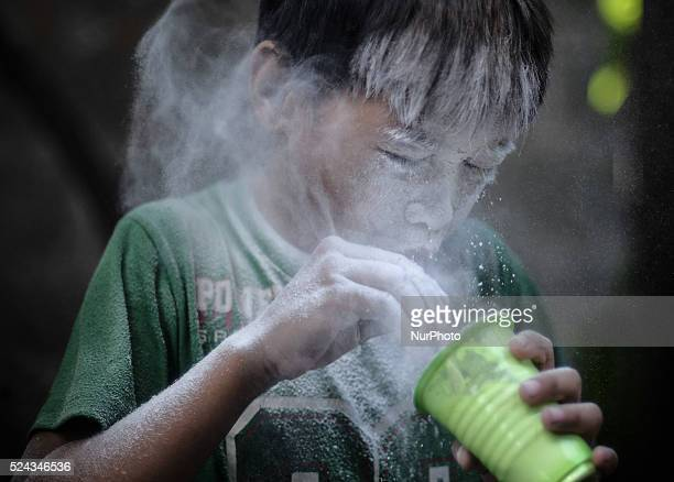 A child blows into a cup filled with flour during parlour games as part of the feast day of Saint Rita of Cascia in Paranaque Metro Manila...