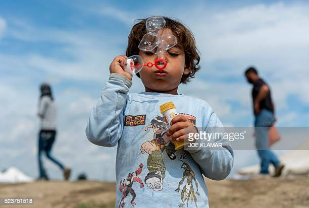 A child blows soap bubbles as she plays at a makeshift camp for migrants and refugees at the GreekMacedonian border near the village of Idomeni on...