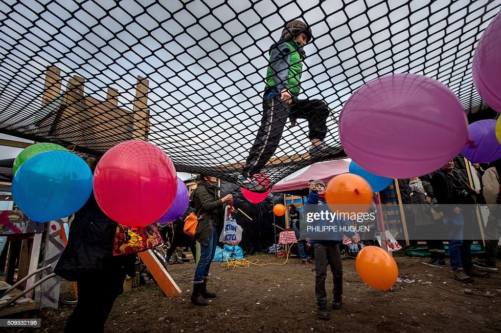 A child bounces on a trampoline at the playground of a shelter used as a school in the so-called 'Jungle' migrant camp in Calais, northern France, on February 6, 2016. HUGUEN