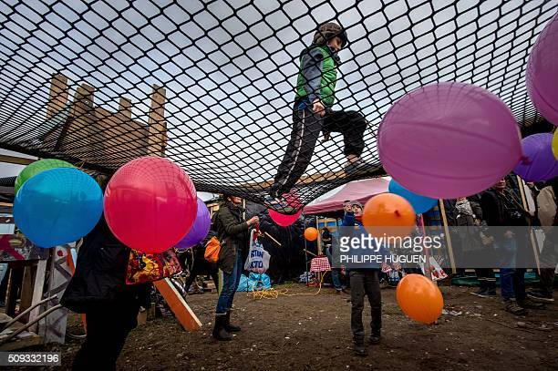 A child bounces on a trampoline at the playground of a shelter used as a school in the socalled Jungle migrant camp in Calais northern France on...