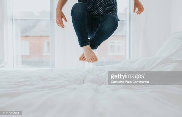child bouncing on a bed - bed stock pictures, royalty-free photos & images