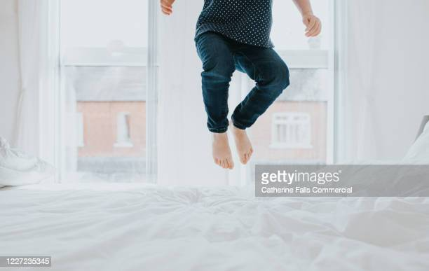 child bouncing on a bed - jumping stock pictures, royalty-free photos & images