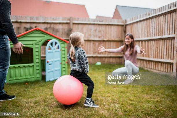 child bouncing on her ball and playing with her parents outdoors - hoppity horse stock photos and pictures