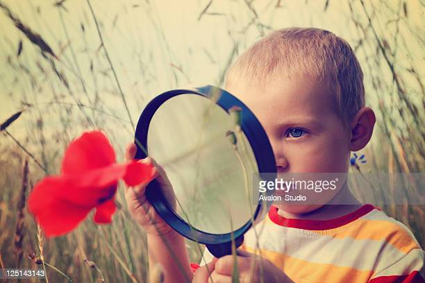 Child boy and magnifying glass
