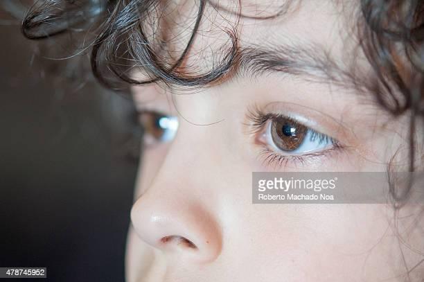 Child boy big brown eyes A closeup of a young boy's dark brown eyes and dark curly hair