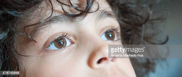Child boy big brown eyes Beautiful Hispanic child boy with curly hair looked up