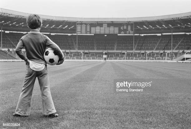 A child Brendan Davey looks at Wembley Stadium holding a soccer ball in his arm London UK 2nd September 1977