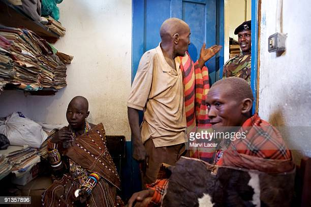 Child bride Seleyian Sekut her uncle Oloitiring'ai Sekut and her husband Olorpala give their statements to a police officer after a raid on their...
