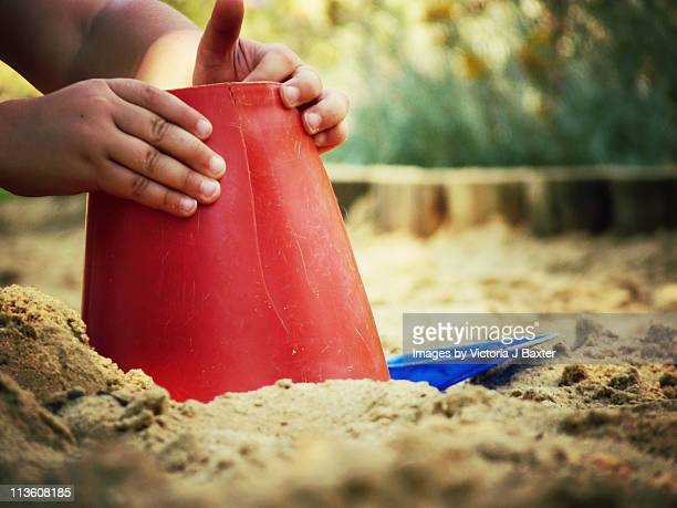 A child building sandcastles in a sandpit