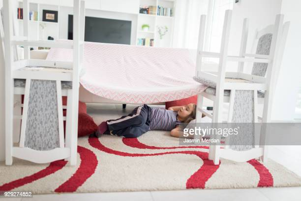 Child building with pillows and chairs