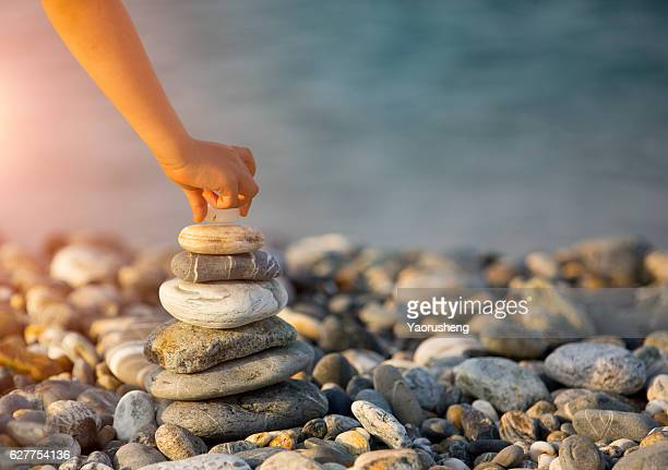 Child  built pyramid from pebbles. Balanced stone pyramid on shore