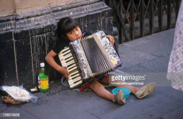 Child Busking In Street Mexico Mexico City Girl Playing The Accordion To Tourists For Money