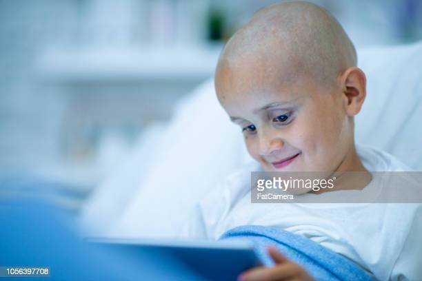 Child cancer patient smiling while watching shows on a tablet in his hospital bed