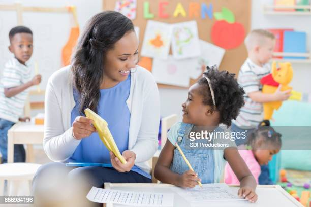 Child care worker and little girl discuss the letter B