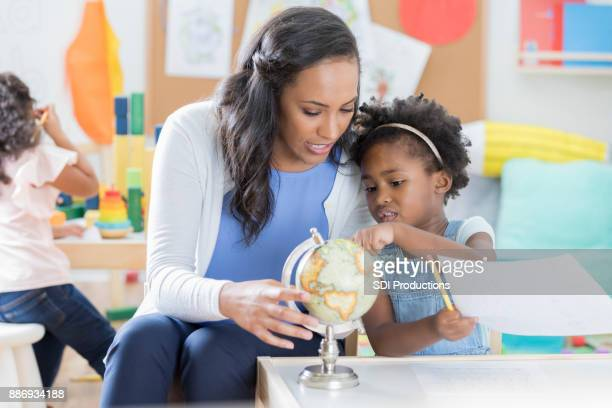 Child care worker answers little girl's questions about a globe