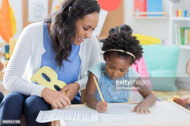 Child care worker helps little girl with handwriting