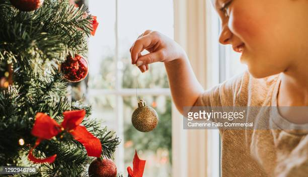 child carefully places christmas baubles onto a christmas tree - symbolism stock pictures, royalty-free photos & images
