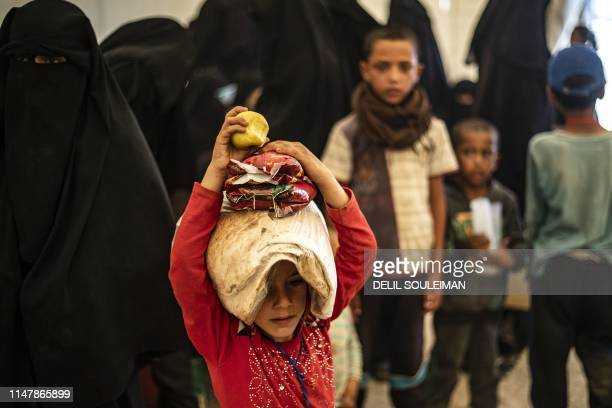 A child carries a bag of bread on his head at the AlHol camp in northeastern Syria's AlHasakeh governorate on June 3 as Kurdish authorities started...