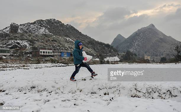 A child carries a big snowball in Shaoguan south China's Guangdong province on January 24 2016 Much of China shivered as a teethchattering cold snap...