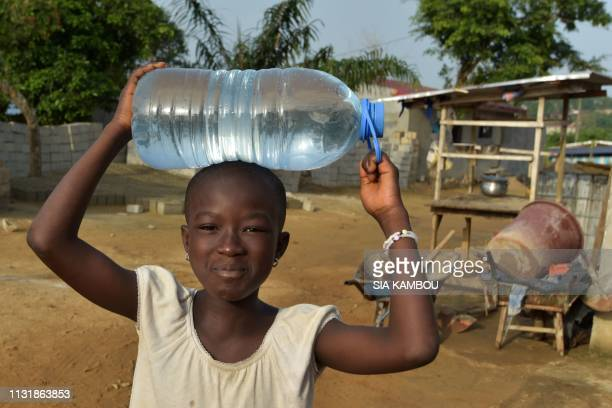 A child carries a bottle filed with the water of the well in the popular district of Yopougon where inhabitants lack of of drinking water in Abidjan...