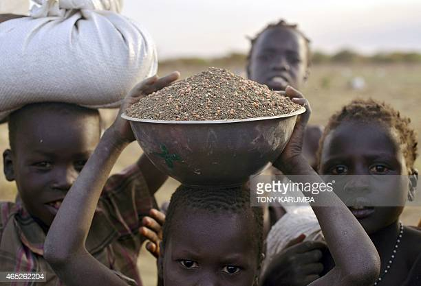 A child carries a bowl of grain mixed with soil after collecting seeds off the ground following a fooddrop at a village in Nyal an administrative hub...