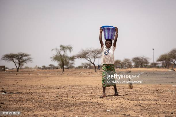 Child carries a bucket of water in Goudebou, a camp that welcomes more than 11,000 Malian refugees in northern Burkina Faso, on International Refugee...