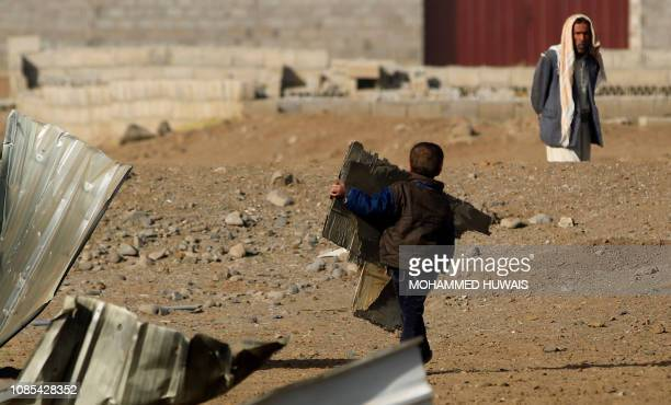 A child carries a corrugated metal following a reported airstrike by Saudiled coalition in the Yemeni capital Sanaa on January 20 2019 Coalition...