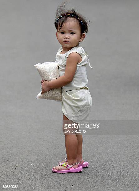 A child carries a kilo bag of rice while her mother buys cheap imported rice from Vietnam at the National Food Authority in suburban Manila on April...