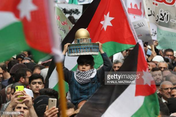 A child carries a mockup of the Dome of the Rock above his head as he is being held by protesters from the Islamic Action Front and others marching...
