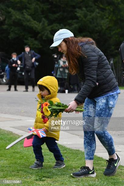 Child carries a toy sword and shield as his mother lays a floral tribute to Britain's Prince Philip, Duke of Edinburgh, the day after his death at...