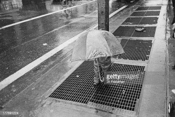 A child carries an umbrella on a rainy street in New York City 1983