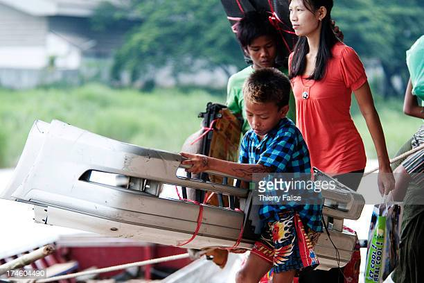 A child carries auto parts at an illegal trading point on the Moei River marking the border between Thailand and Myanmar