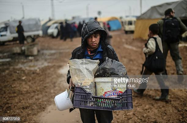 TOPSHOT A child carries belongings as refugees arrive at the Turkish border crossing gate as Syrians fleeing the northern embattled city of Aleppo...