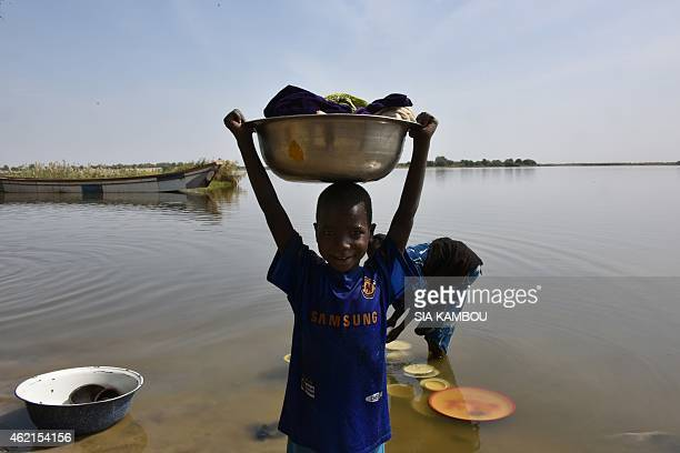 A child carries clean clothes in Bol on January 25 2015 in the waters of Lake Chad which borders Chad Nigeria Niger and Cameroon Chad's President...