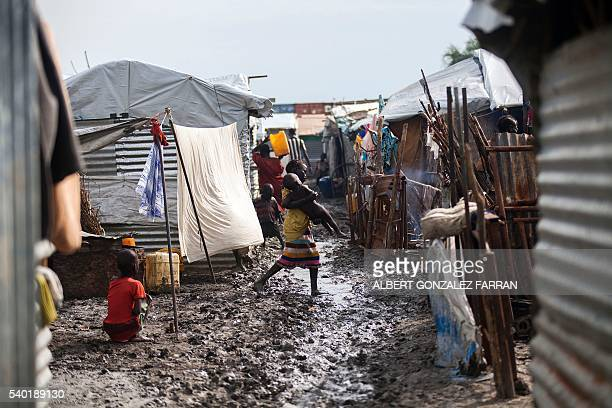TOPSHOT A child carries her young relative in the Protection of Civilians site in Malakal on June 14 2016 The rainy season started and made the...
