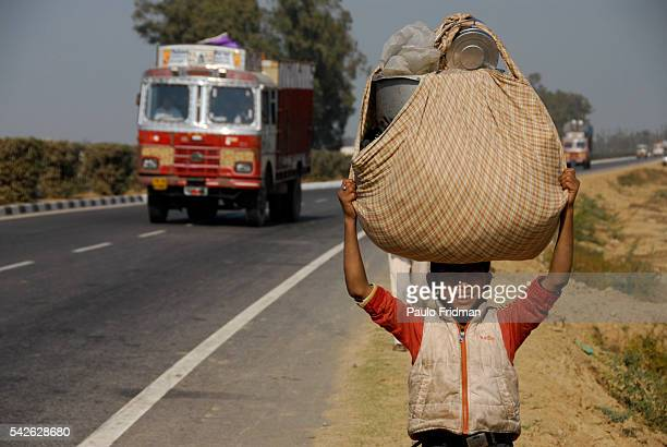 Child carring a bag of traps in a road in Agra Uttar Pradesh India