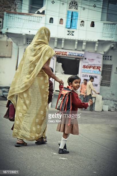 Child carrying a bag looks back at the camera as her mother takes her hand and leads her off toward school. Udaipur, 2011.